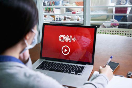 Watching CNN+ on a laptop.
