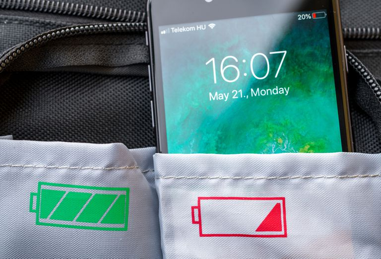 An iPhone with a low battery sticking out of a pocket of a bag.