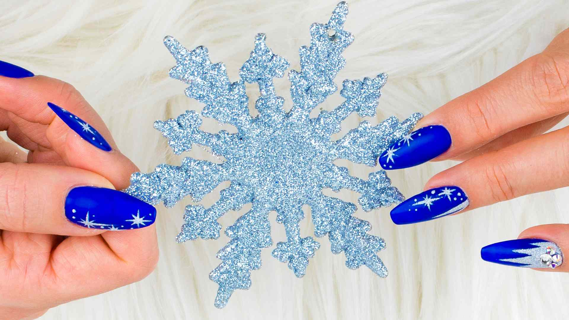 A woman with blue nails holding a snowflake looking like a live-action Elsa from Frozen.