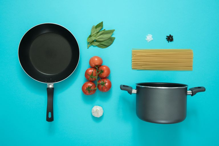 A stock photo of kitchen equipment next to an assortment of ingredients for a pasta dish, all laying on a bright teal background. There are two pieces of equipment: a frying pan and a stock pot. There are six ingredients shown: tomatoes, garlic, a bunch of leafy greens/herbs, dry pasta and two small piles of spices.