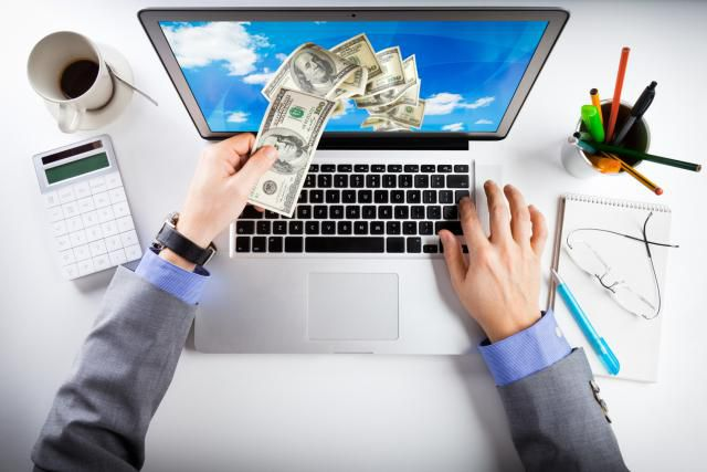 Hand putting money in computer