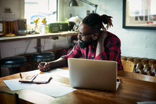 Male designer uses laptop in office