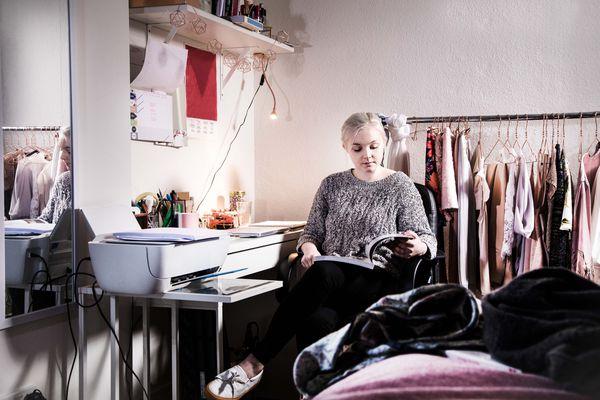 Female university student in dorm at desk with printer.