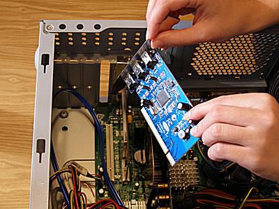 Picture of someone holding an expansion card taken from a computer motherboard