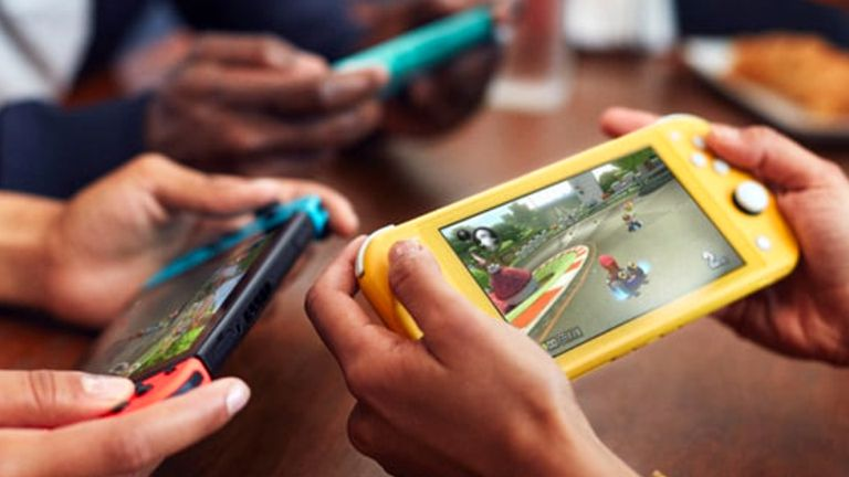 Three people playing Super Mario Kart 8 on a Nintendo Switch and two Nintendo Switch Lite consoles.