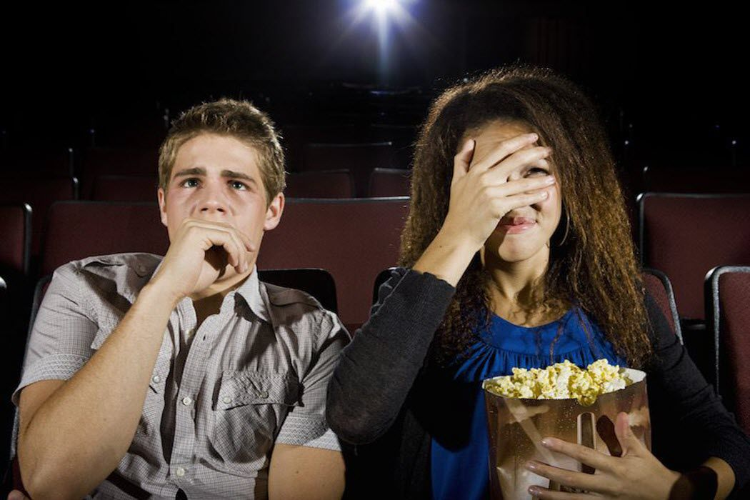 A young couple watching a scary movie in a dark theater.