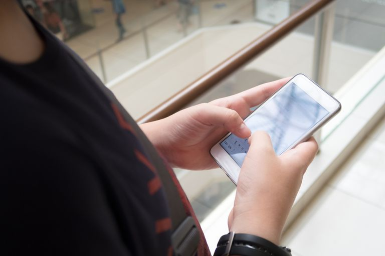 A young person holding a phone.