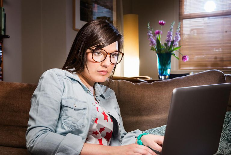 Woman working on laptop at home at night