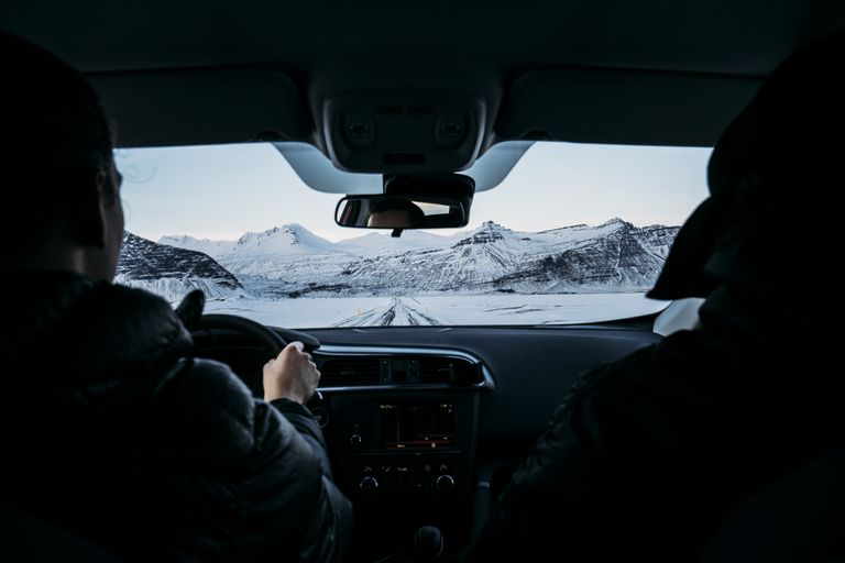 Men driving car through snow covered landscape, Iceland