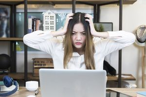 Stressed woman using laptop computer at home