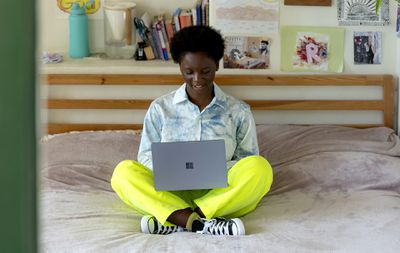 A woman sitting cross-legged on her bed while using a Microsoft Surface Laptop.