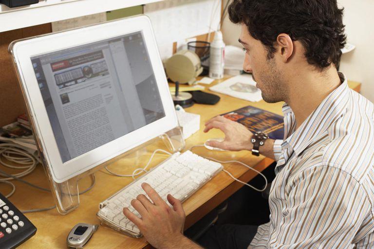 Male office worker at workstation, view over shoulder