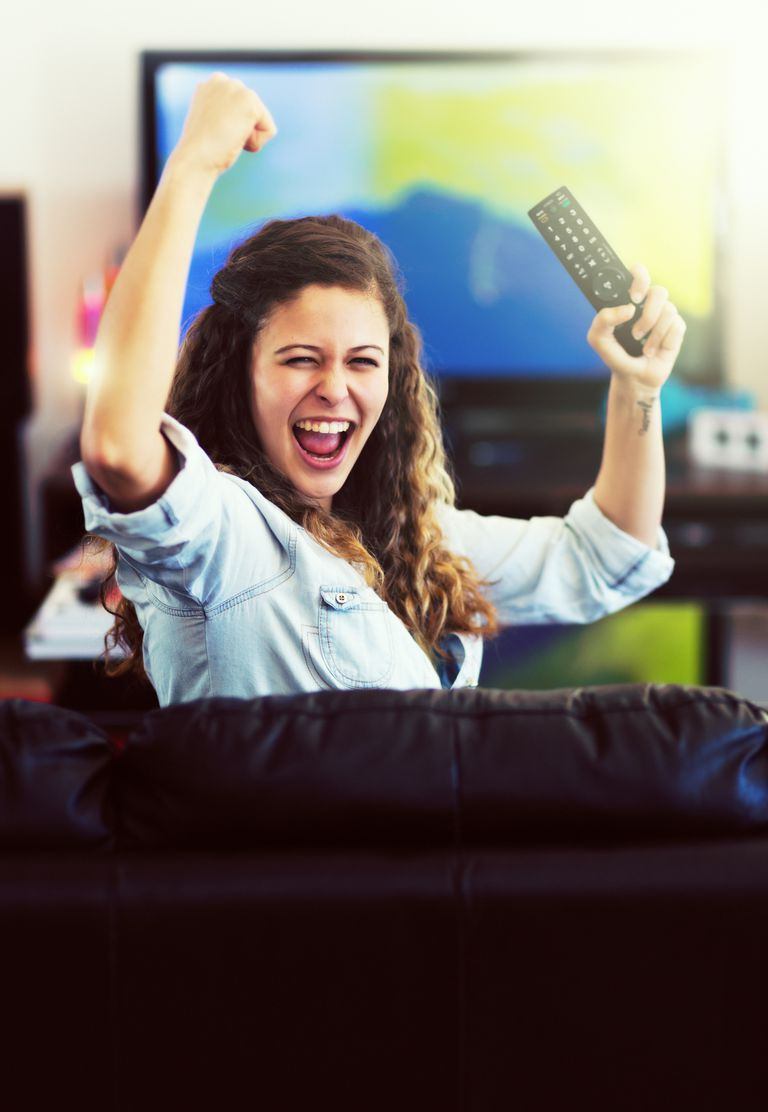 Pretty sports enthusiast holds TV remote, cheering her team