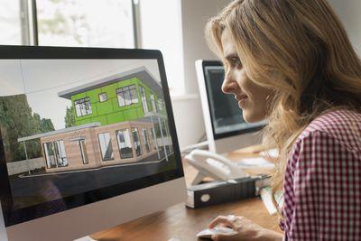Graphic designer looking at digital rendering on computer screen