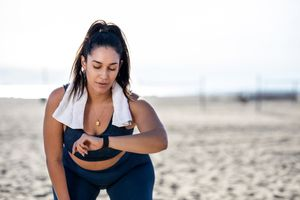 A woman looking down at her fitness tracker while sitting on the beach and wearing workout clothing