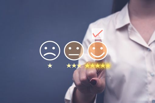 A person tapping a smiley face in the foreground, next to a normal face and sad face.