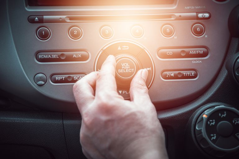 A passenger reaches over to adjust the HD radio.