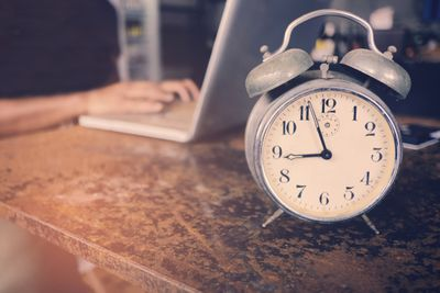 Cropped Hand Of Person Using Laptop By Alarm Clock At Table
