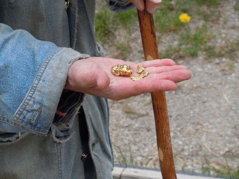 Midsection Of Man Holding Gold Nugget Outdoors