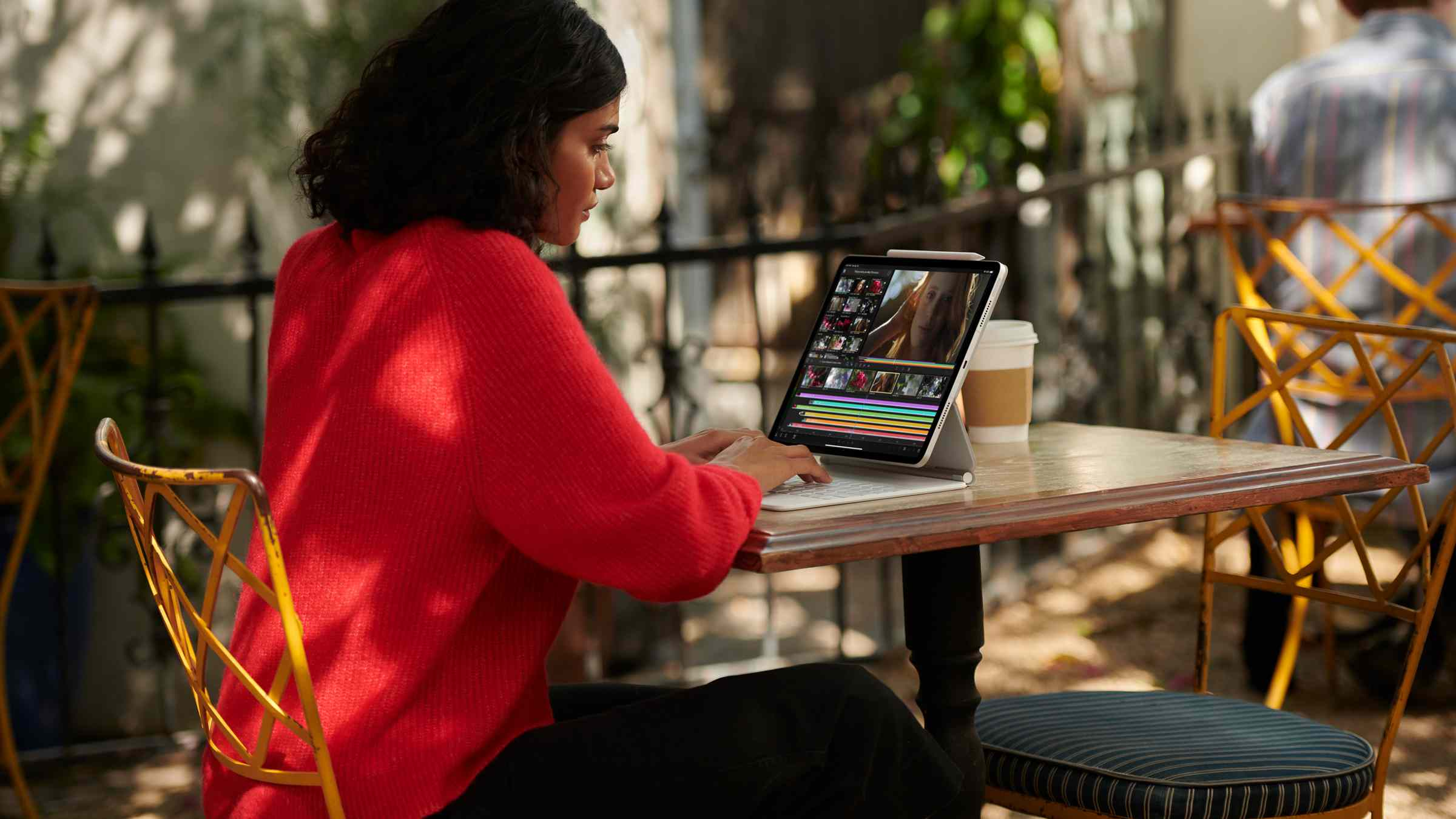 Someone using an Apple iPad Pro with an M1 chip in it while sitting in an outdoor cafe.