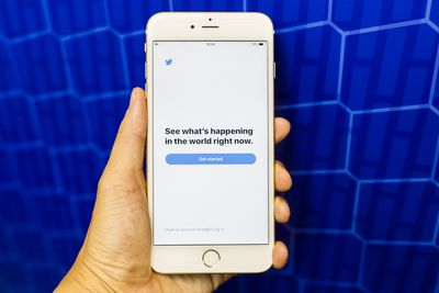 A hand holding an iPhone showing the Twitter Get Started screen, all up against a bright blue background.