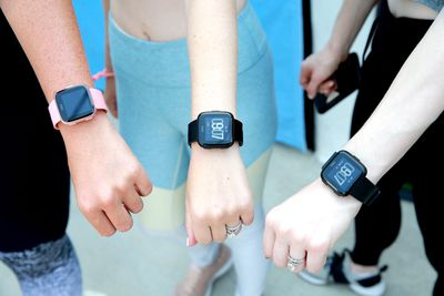 Three women wearing the Fitbit Versa smartwatch on their wrists.