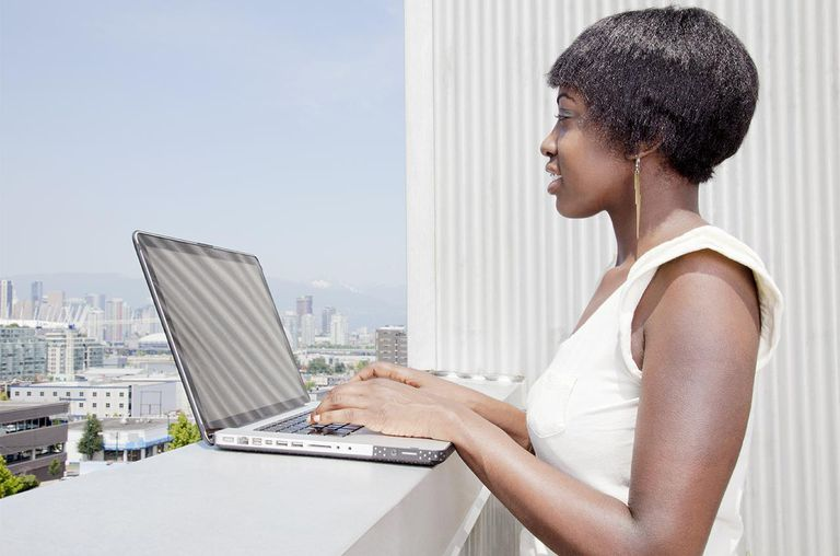 Woman using laptop on patio overlooking city.