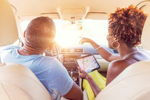 Couple in car using ipad with navigation