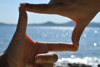 View finder frame from hands with view to sea and mountains