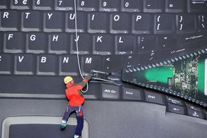 Laptop keyboard being unzipped by a mountain climber revealing a motherboard underneath.
