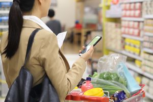 A woman in a grocery store with a cart full of food, using the shopping list that's on her iPhone.