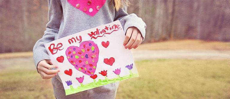 girl holding Valentines Card with pink heart