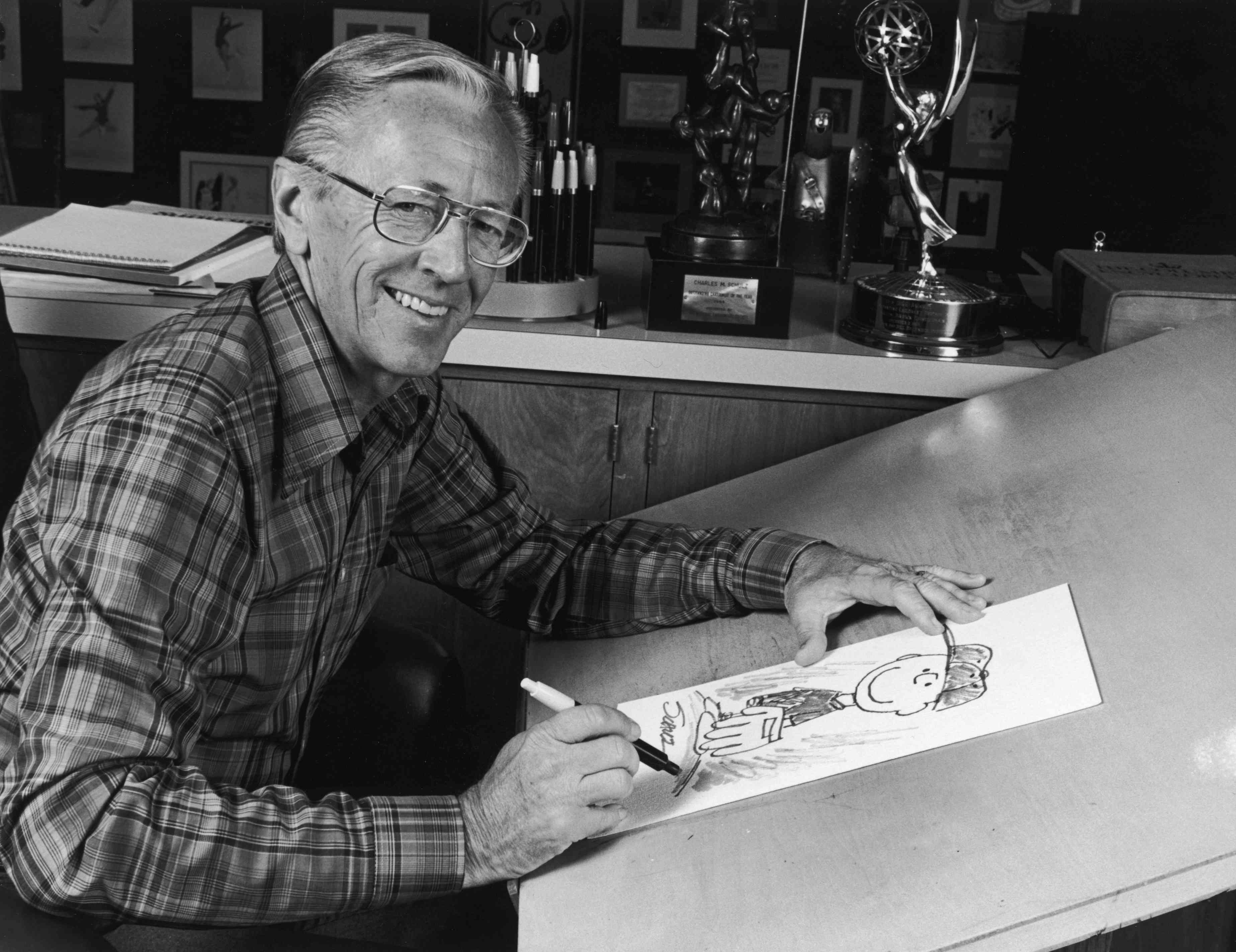 1978: Portrait of American cartoonist Charles M Schulz (1922 - 2001), creator of the 'Peanuts' comic strip, sitting at his studio drawing table with a picture of his character Charlie Brown and some awards behind him. Schulz created the comic strip in 1950.