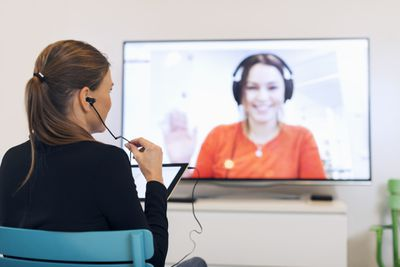 Image of woman having a video meeting on a television