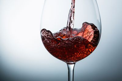 Close-Up Of Red Wine Being Poured In Glass Against White Background