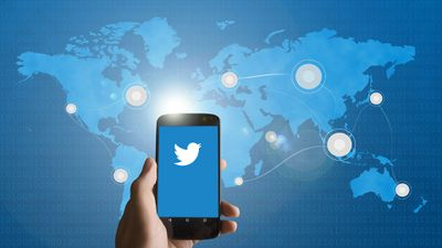 Hand holding a smartphone with the Twitter icon in front of a global map.