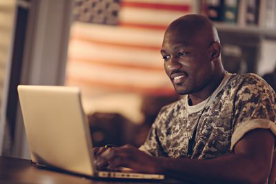 Active duty service member using a laptop computer.