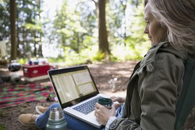 Woman using computer while camping