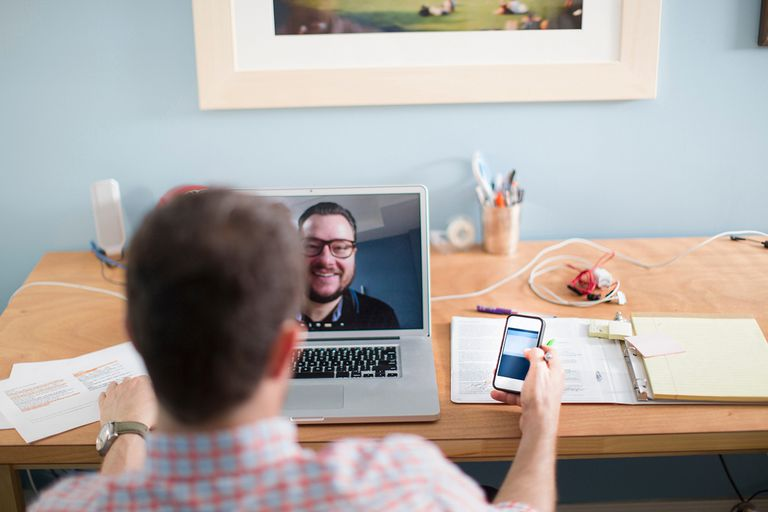 Man at his desk on Facetime on his laptop