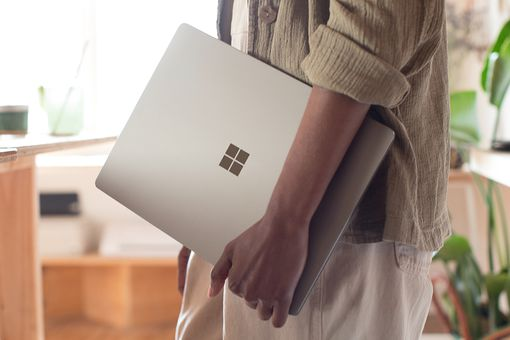 A woman carrying a Surface Laptop computer