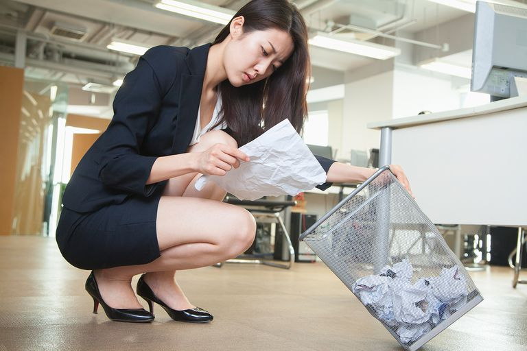 Young businesswoman reading piece of paper from the trash can in office.