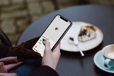 Someone holding an iPhone X with Find My for people displayed on the screen.
