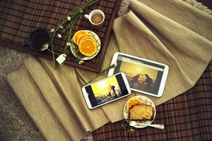 Image of a breakfast tray on blankets, with tea, a biscuit, orange slices, a smart phone and a tablet.