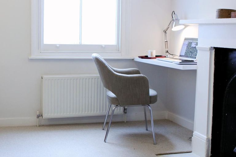 An empty chair in front of an open laptop in a home office