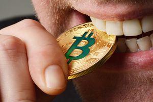 Man biting a Bitcoin coin