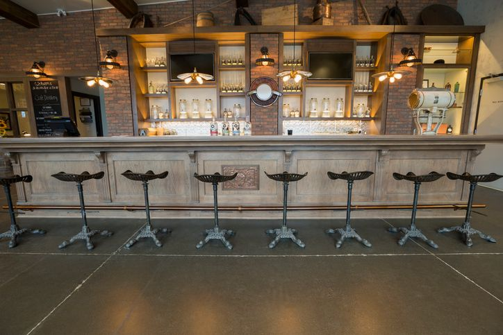 Stools lined along empty distillery bar
