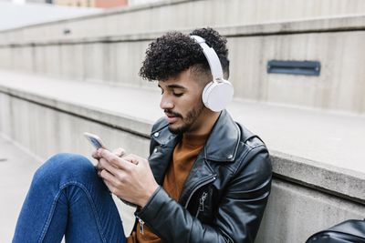 A man leaning against some concrete stairs looking at his smartphone while wearing headphones