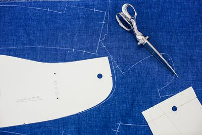 Overhead view of pattern preparation to make blue suit jacket
