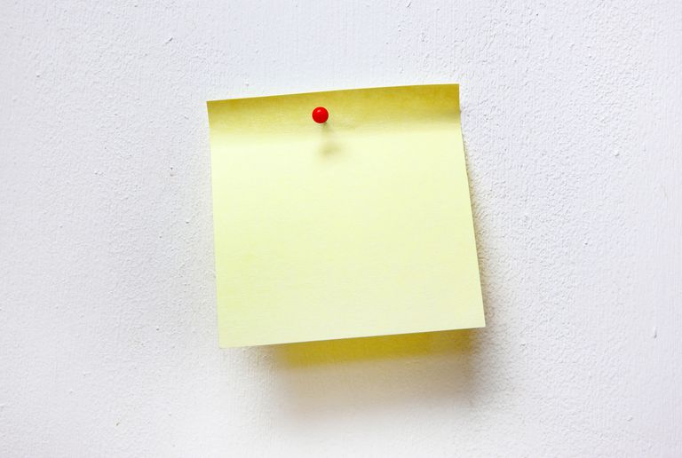 Photo of a blank sticky note pinned to a wall