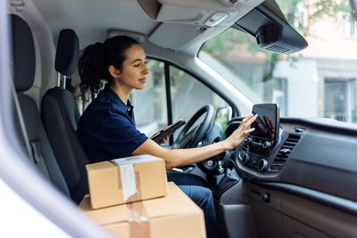 courier sitting in the van and entering delivery address in the car navigation device
